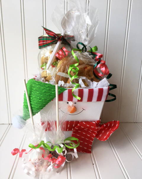 holiday character box filled with a cookie jar, 3 cookies, and two cake pops, wrapped in cellophane and finished with a bow